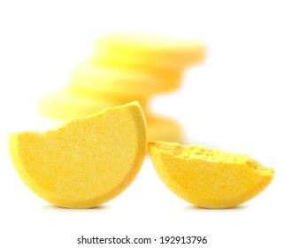 Broken pills of vitamin C on white background