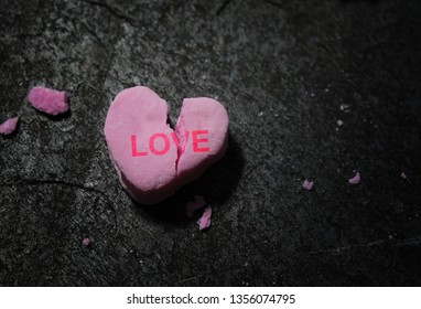 Broken pink candy heart with Love text