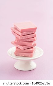 Broken pink Ruby chocolate bar pieces, made from ruby cocoa beans, piled up on a miniature cake stand