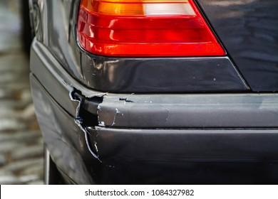 Broken plastic car trim panel, cracked bumper with hole.