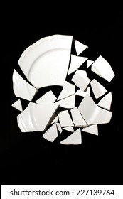 Broken plate on a black background, a try to restore the whole from the pieces