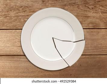 Broken plate on wood table