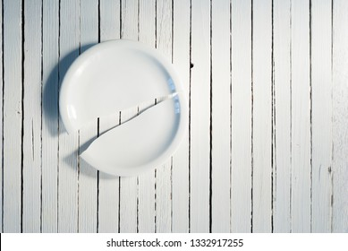 broken porcelain plate on white wooden background