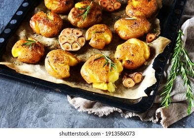 Broken potatoes baked with rosemary on a baking sheet