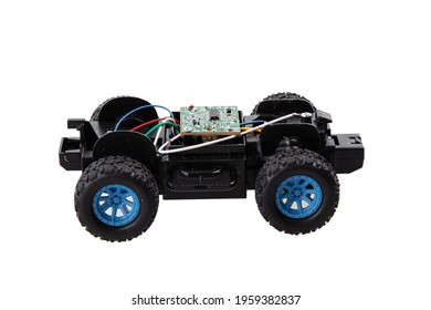 Broken radio-controlled toy car with electronic components on a white background
