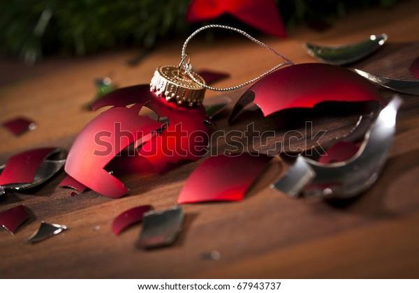 bauble de Navidad roja rota y sombras en el suelo de madera