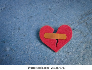 Broken red heart with a bandaid, on blue