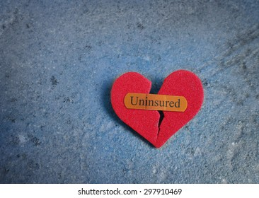 Broken red heart with a bandaid and Uninsured text -- lack of health insurance concept