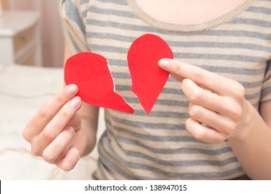 Broken red heart in beautiful female hands (fingers) in bedroom. Conflict in couple, problems, divorce and pain concept.