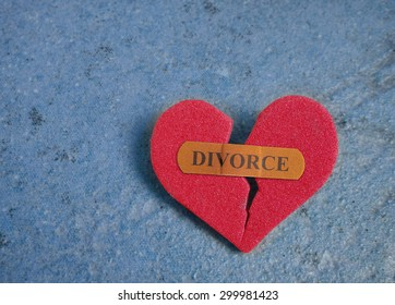 Broken red heart with a Divorce bandaid, on blue