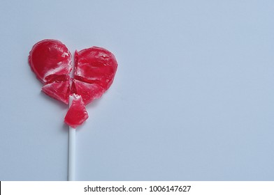 A broken red heart lollipop symbolizing a broken heart