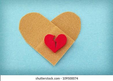 broken red heart on a heart shaped bandage