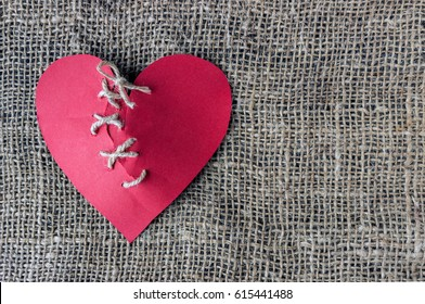 A broken red heart. Sewn thread. The concept of divorce, separation, quarrel.