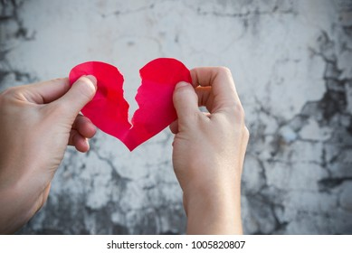 Broken red heart tear by woman, lady or female hands over cracked dark grey old grunge wall showing strong emotion of sad or sorrow fail love on Valentine's day, unsuccessful love relationship concept
