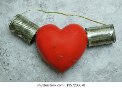Broken red heart with tin can phone that the rope was cut off. Miscommunication concept