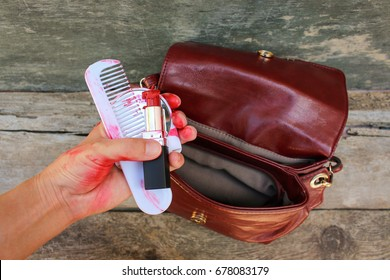 Broken red lipstick, mirror, comb in women hand.