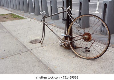 Broken, rusty bicycle with missing front wheel and dropped chain locked to a metal pole on a sidewalk