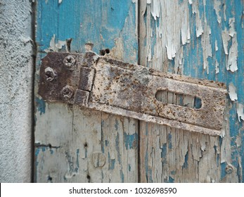 Broken rusty latch on the abandoned turquoise door. Weathered vintage wooden door peeling turquoise paint with rusty latch.
