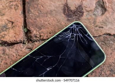 Broken screen glass of mobile smartphone on the brick floor