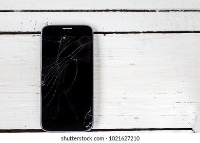 Broken screen of the modern smartphone, on a white wooden table. Top view