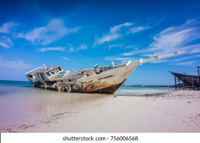 Broken ship at beach with blue sky