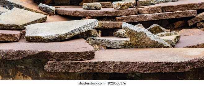 Broken slabs of stone scattered and layered on top of one another to create a background.