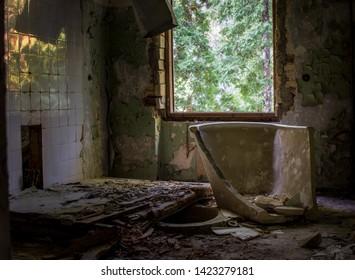 Broken sludge treatment tub, bath near the window in abandoned sanatorium in Baldone city, Latvia