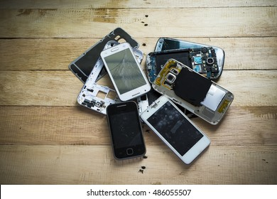 Broken smart phone with tone and wooden texture background