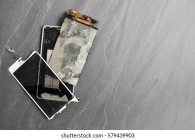 Broken smartphone display, shattered glass and touch unit. Grey stone background