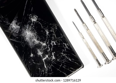 broken smartphone and screwdriver for repair on white background, isolated
