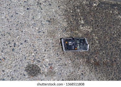 broken and smashed run over smartphone on a stained asphalt road