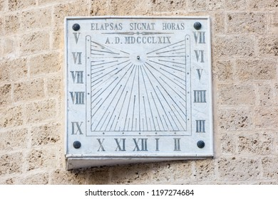 Broken squared stone sun dial with roman numbers on the cathedral in Foggia, Puglia, Italy