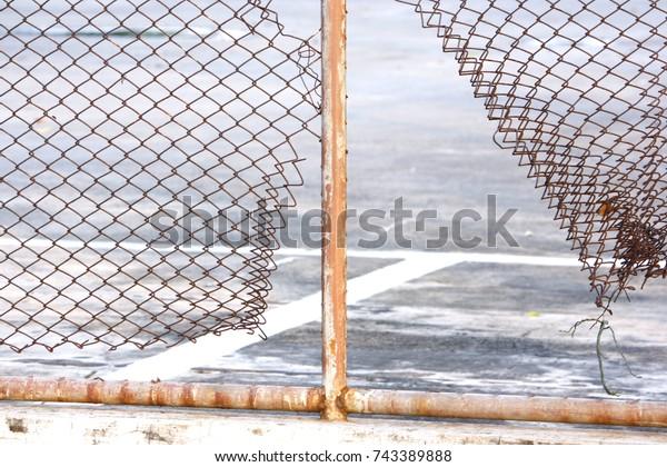 Broken steel mesh of metal fence of a basketball court in residential neighborhood ,Tennis and basketball court behind fence mesh netting at school