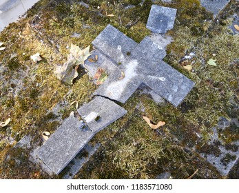 A broken stone cross on an old mossy grave at the Montmartre Cemetery