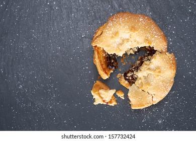 A broken sweet Christmas mince pie on a Slate cooling board.