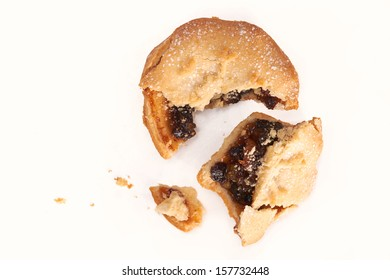 A broken sweet Christmas mince pie on a white background.