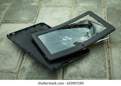 Broken tablet pc on pavement