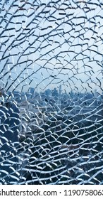 Broken tempered glass on high rise building with city view in background.