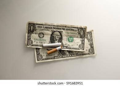 Broken tobacco cigarette and money dollar bill. Nicotine addiction.