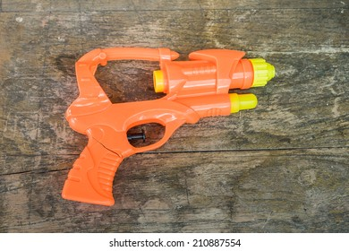 The broken toy gun on the wood background