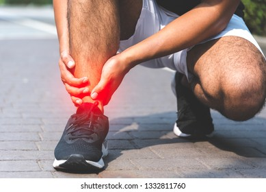 Broken twisted ankle. Runner touching foot in pain due to sprained ankle