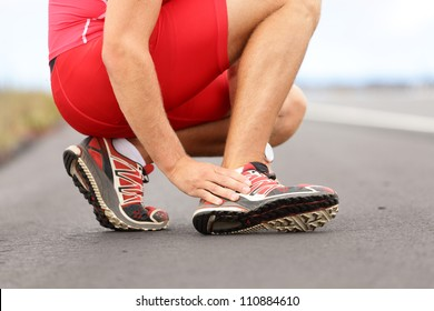 Broken twisted ankle - running sport injury. Male runner touching foot in pain due to sprained ankle.