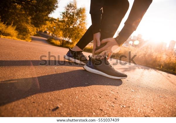 Gebrochener Knöchel - Laufende Sportverletzung. Athletischer Mann-Läufer, der den Schmerz durch verstauten Knöchel berührt