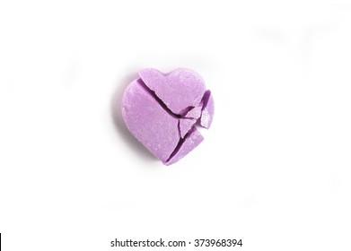 Broken Valentine's Day purple candy heart on white background