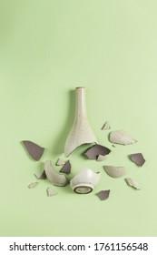 A broken vase against a green background