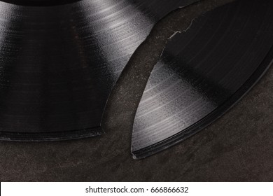 Broken vinyl record on a textured metal surface