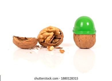 Broken walnut with walnut wearing helmet for safety with white background