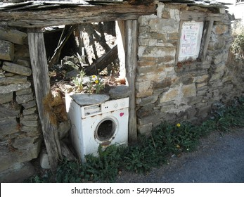 A broken washing machine in an old abandoned house in a small village on The Way of St. James, Camino de Santiago, Camino Francés. Galicia, Spain.