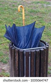 Broken wet umbrella in garbage bin