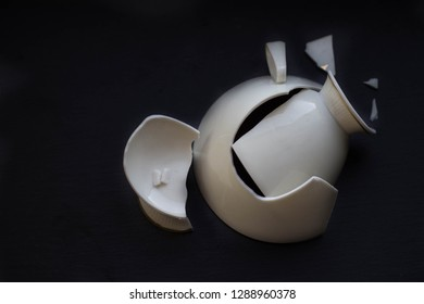 broken white china cup on black background